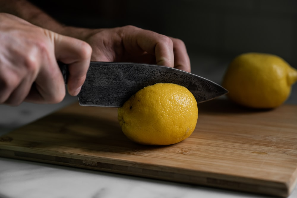 person holding yellow lemon fruit