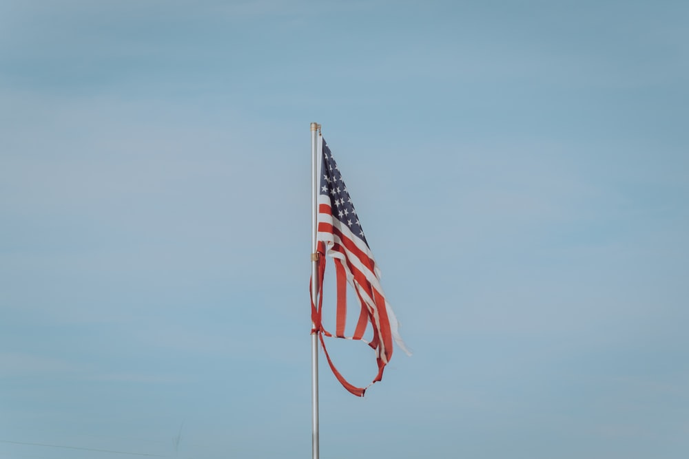 us a flag on pole under blue sky during daytime