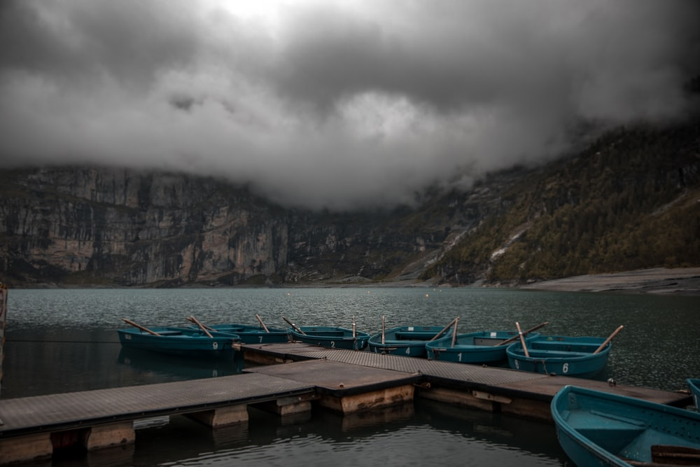 green boat on dock near mountain during daytime
