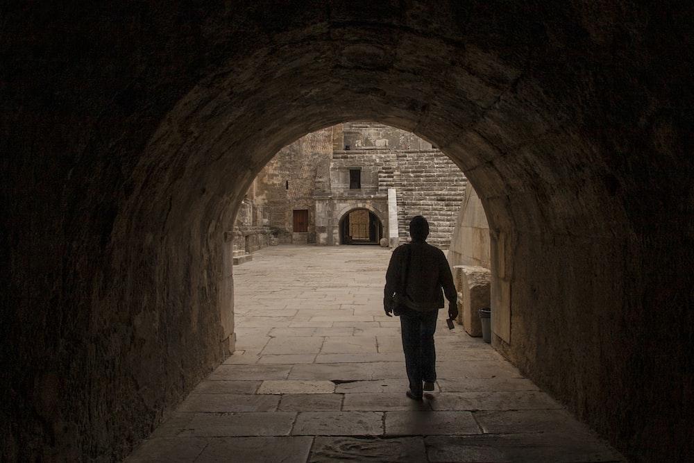 man in black jacket standing on brown brick hallway