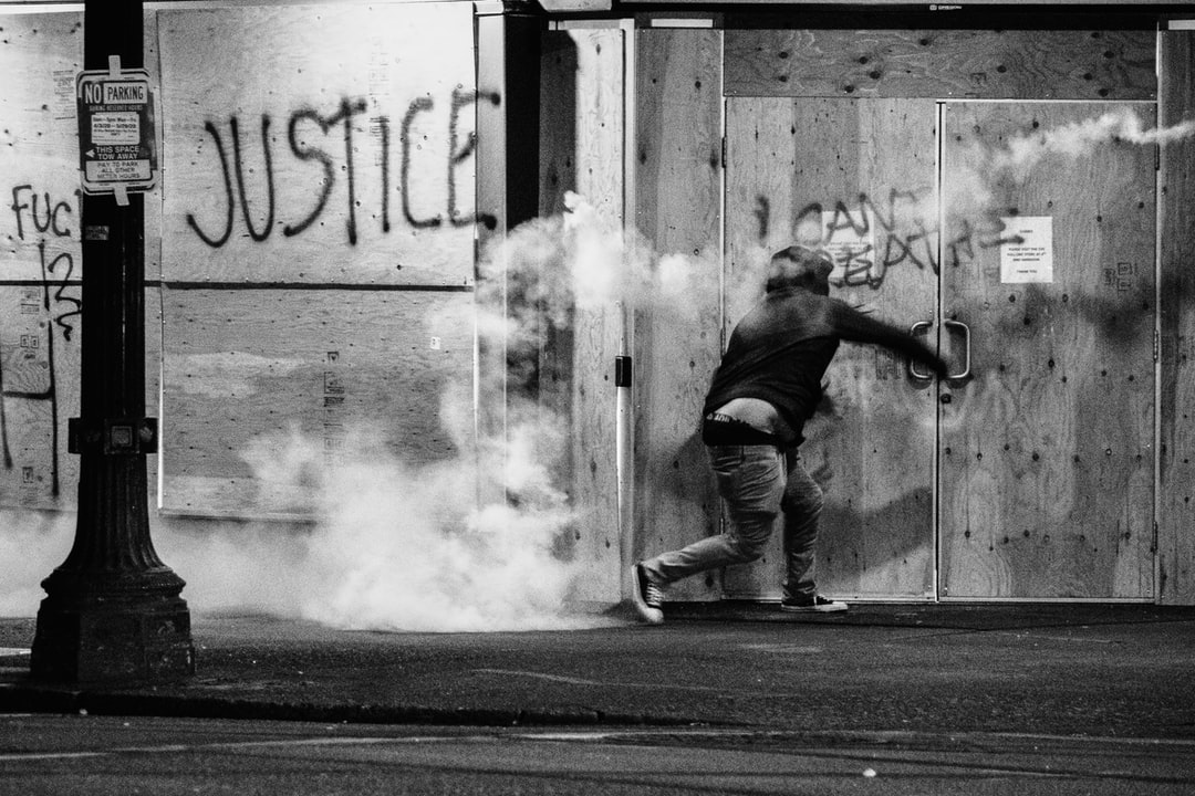 Protester throws tear gas canister back at police during a Black Lives Matter protest in Portland, Oregon. People have been protesting police brutality and the deaths of several members of the Black community - sparked by the recent death of George Floyd.