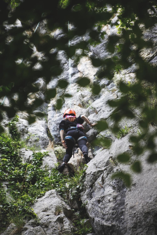man in black t-shirt climbing on rocky mountain during daytime