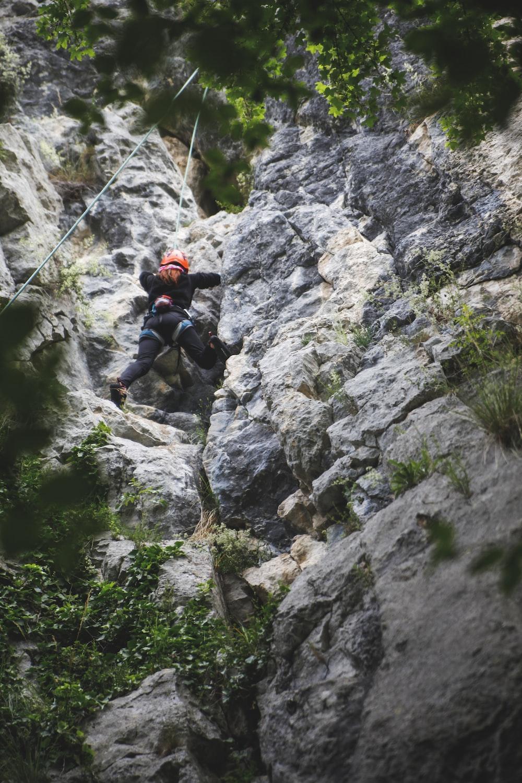 man in black jacket climbing on rocky mountain during daytime