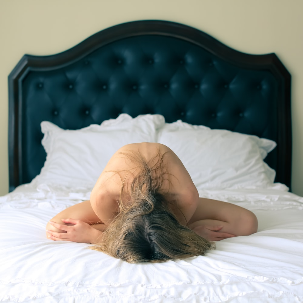 woman lying on bed covering her body with white blanket