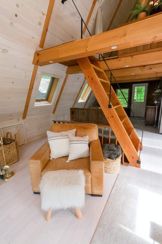 brown wooden staircase near white sofa