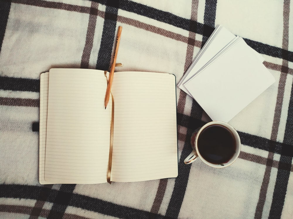 white book beside white ceramic mug on white and black plaid textile