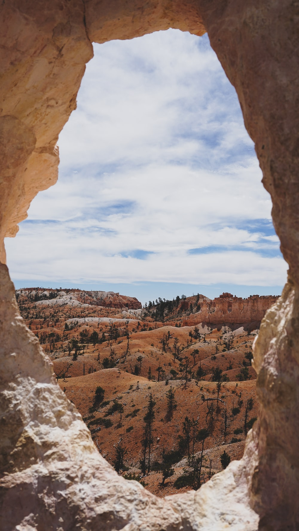 brown rock formation under white clouds and blue sky during daytime