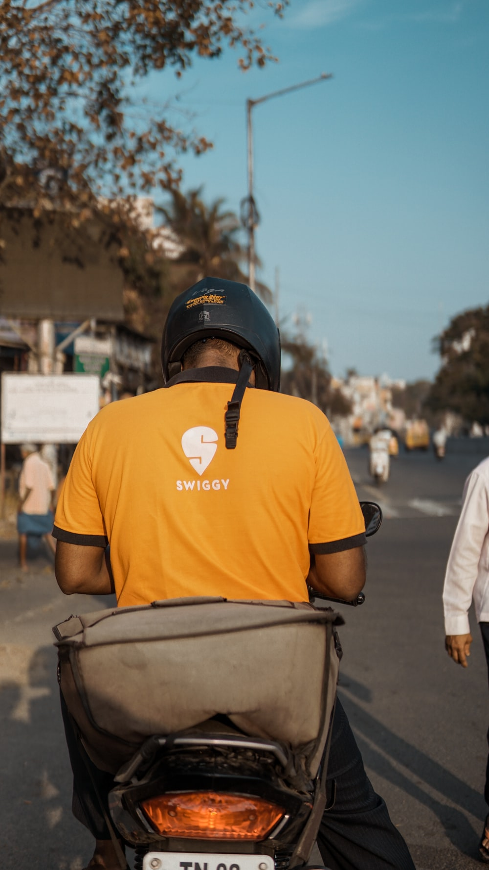 man in orange crew neck t-shirt wearing black helmet
