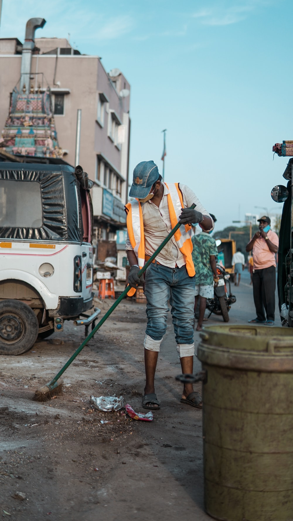 man in orange vest and blue denim jeans standing on white truck during daytime