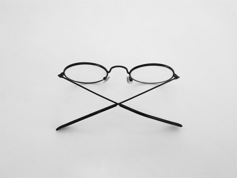 black framed eyeglasses on white surface