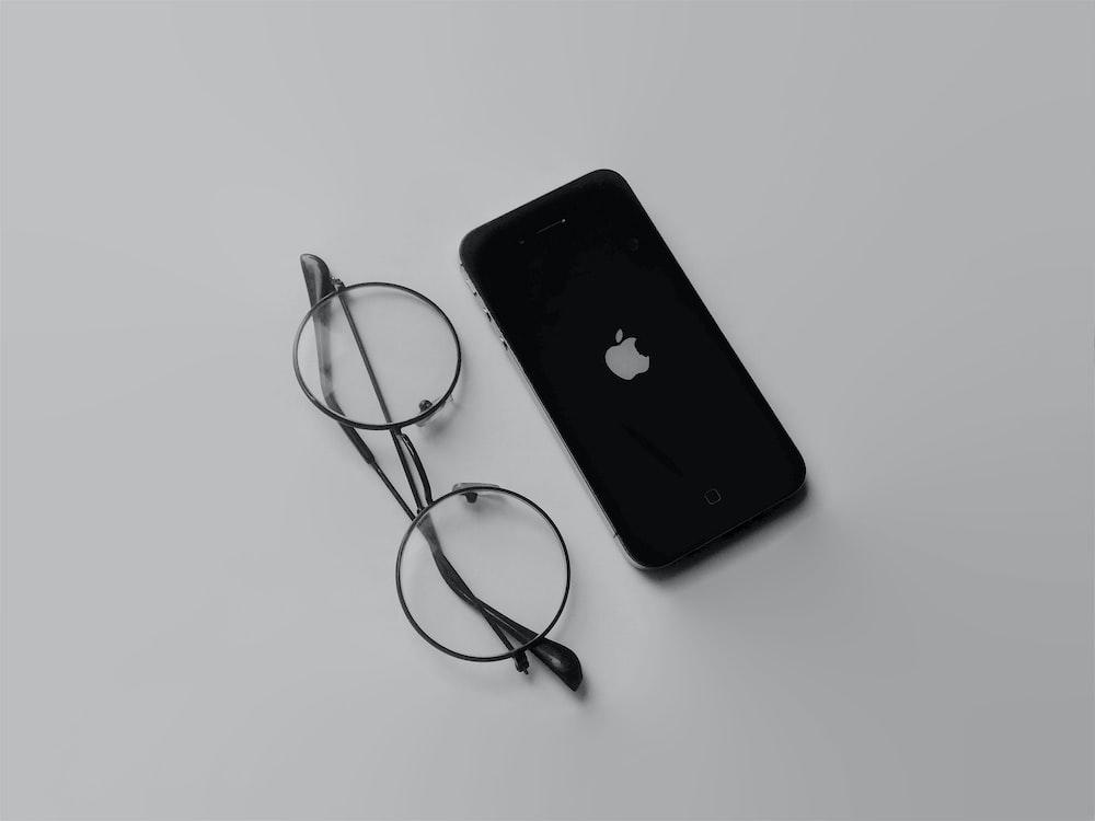 black iphone 4 beside black framed eyeglasses
