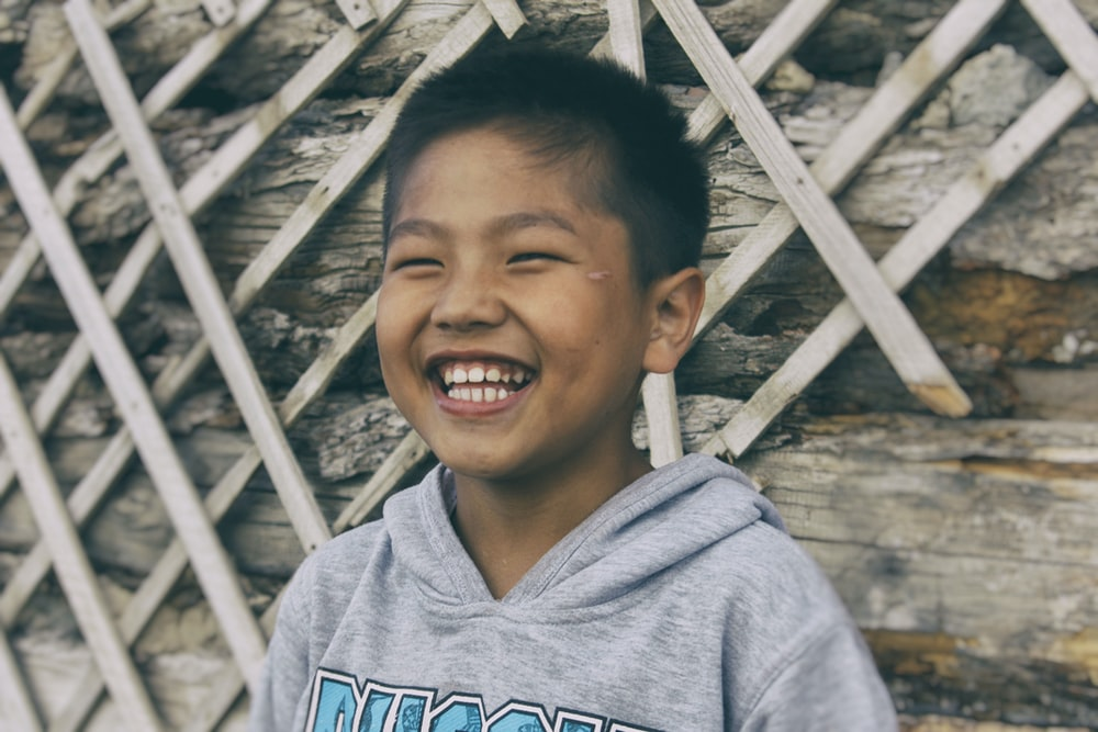 smiling boy in gray and blue hoodie