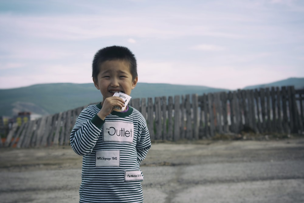 boy in black and white striped long sleeve shirt drinking from white plastic cup