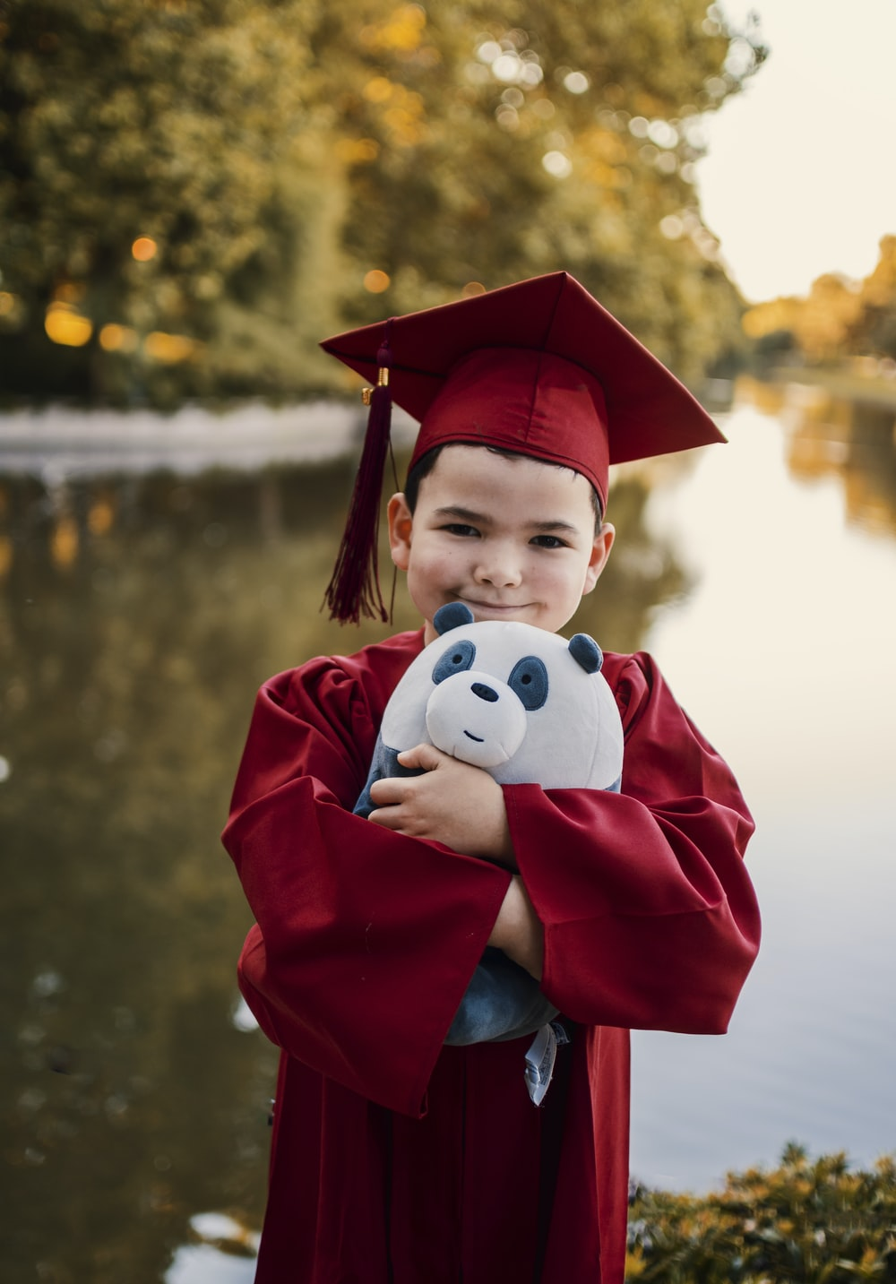 boy in red academic dress with white and black panda plush toy