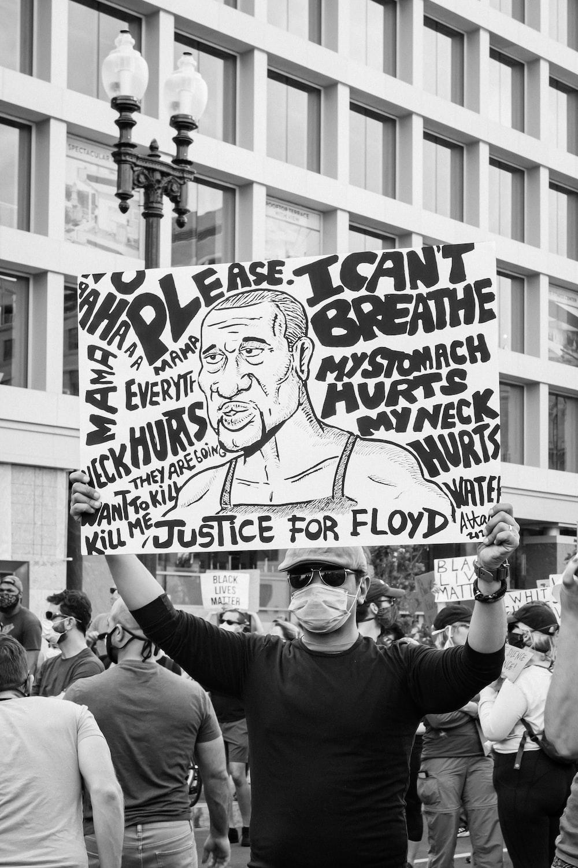 grayscale photo of man holding happy birthday signage
