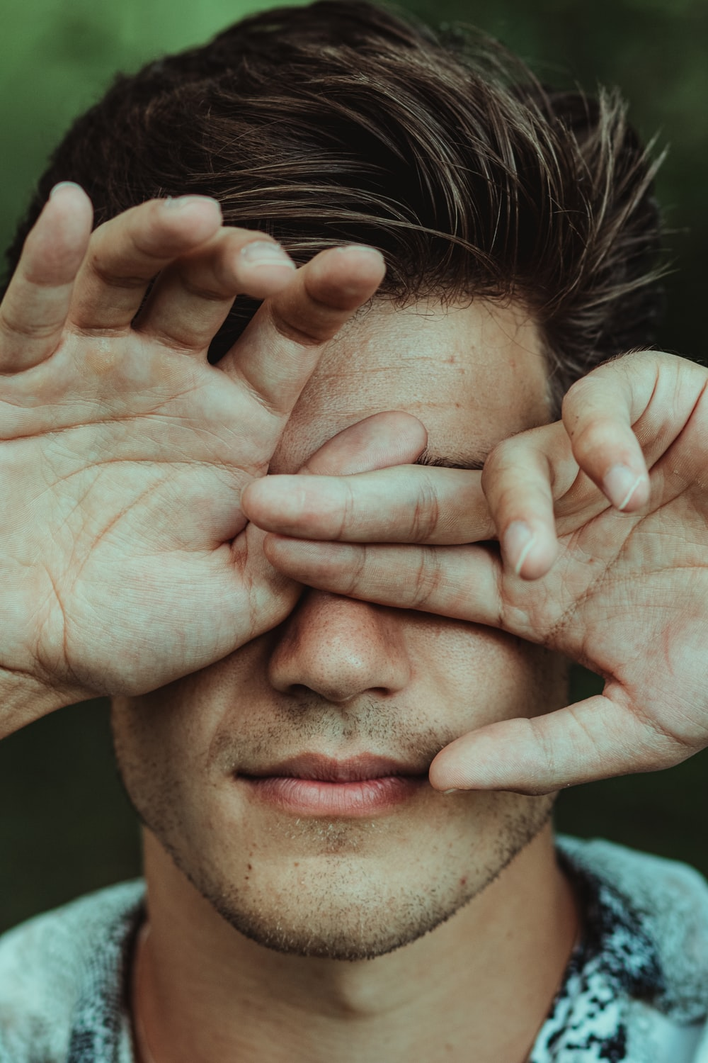 man holding his face during daytime