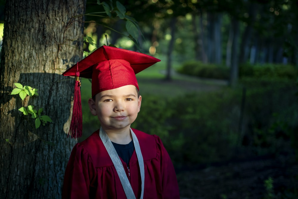boy in blue academic dress and red academic hat