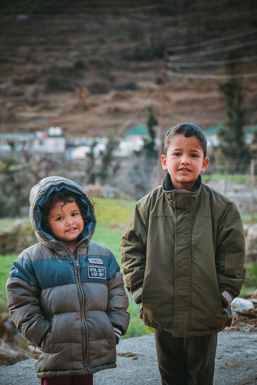 man in gray jacket beside boy in gray jacket