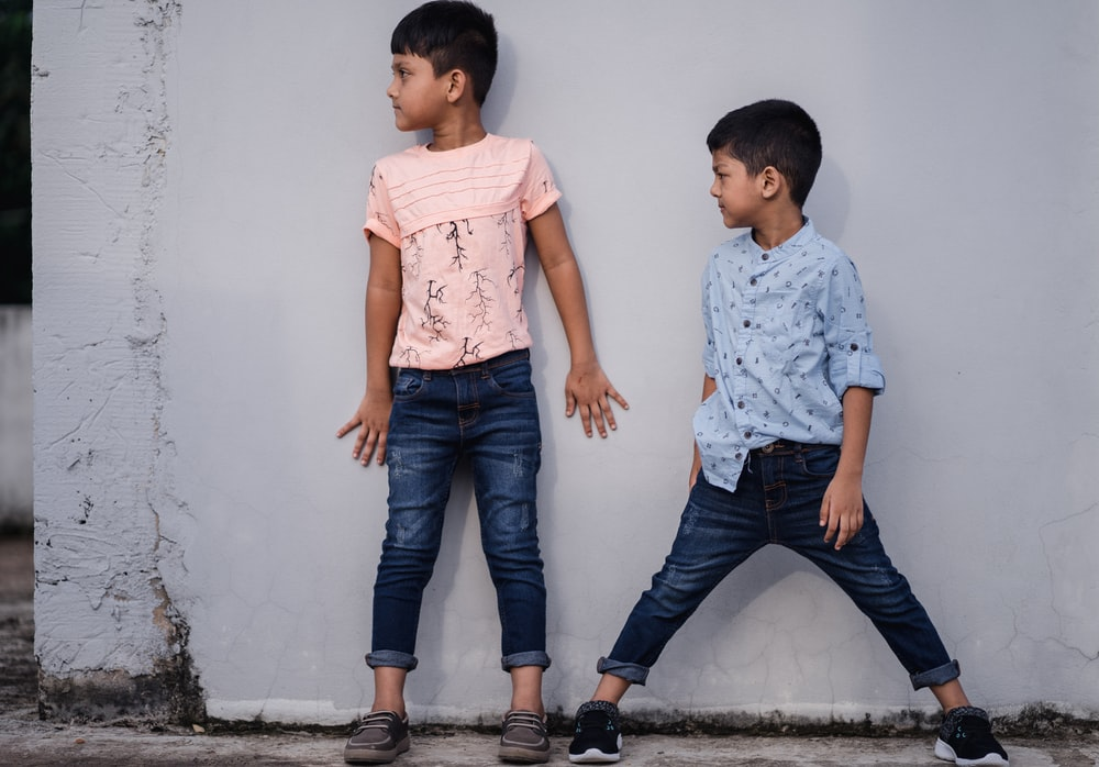 boy in white and pink floral button up t-shirt and blue denim jeans standing beside