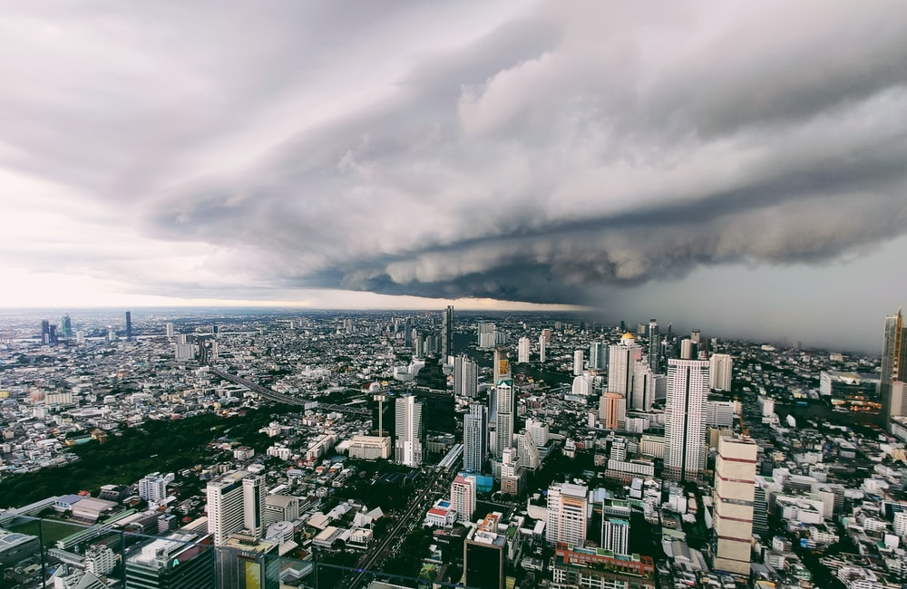 city with high rise buildings under white clouds during daytime