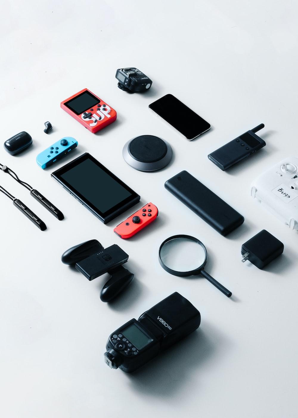 black and silver camera beside black smartphone and black smartphone