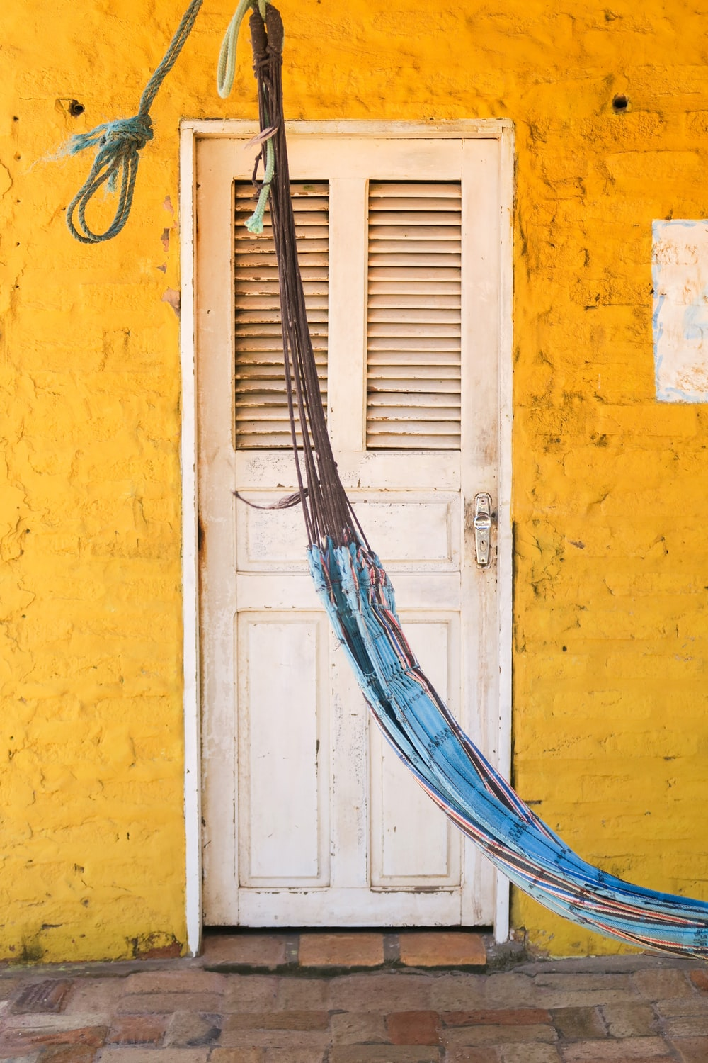 brown wooden ladder leaning on yellow painted wall