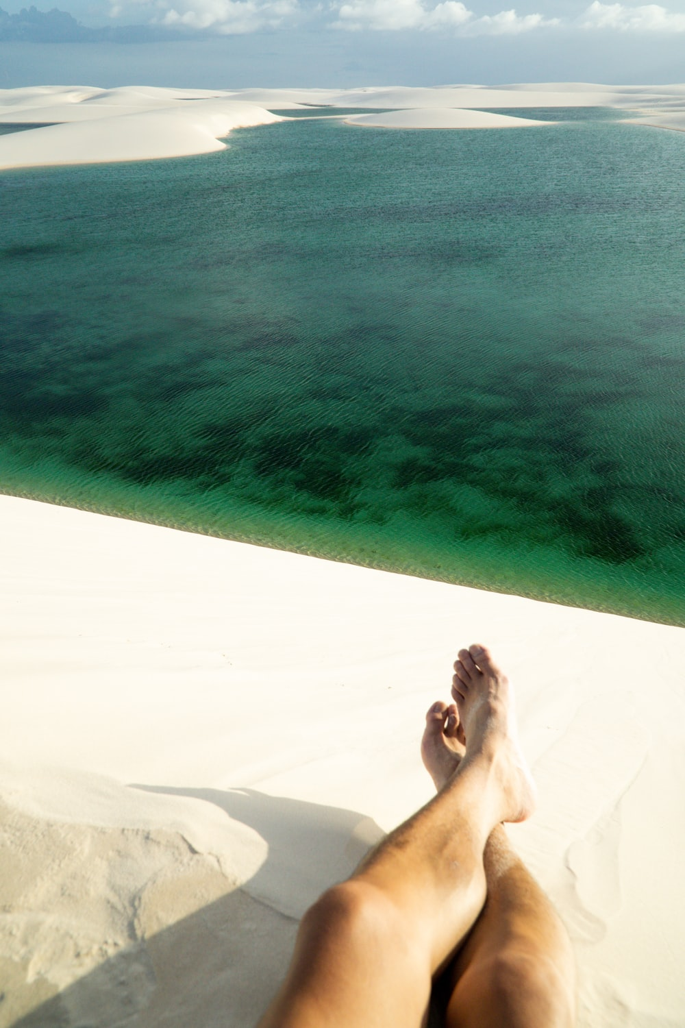 woman lying on white sand near body of water during daytime