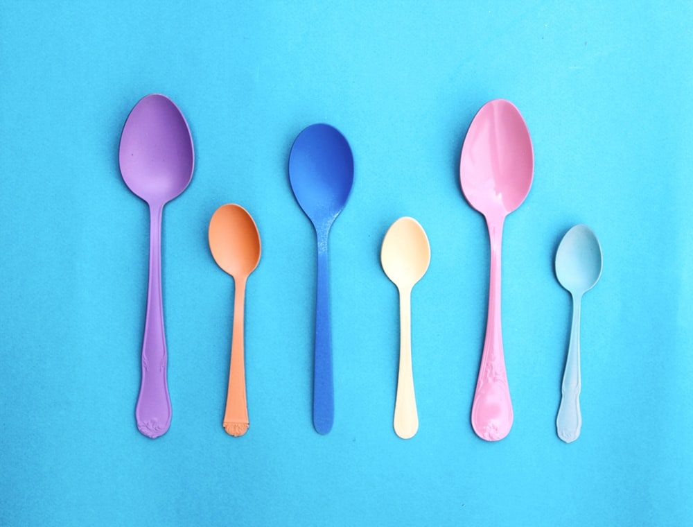 pink plastic spoon on pink and white polka dot textile