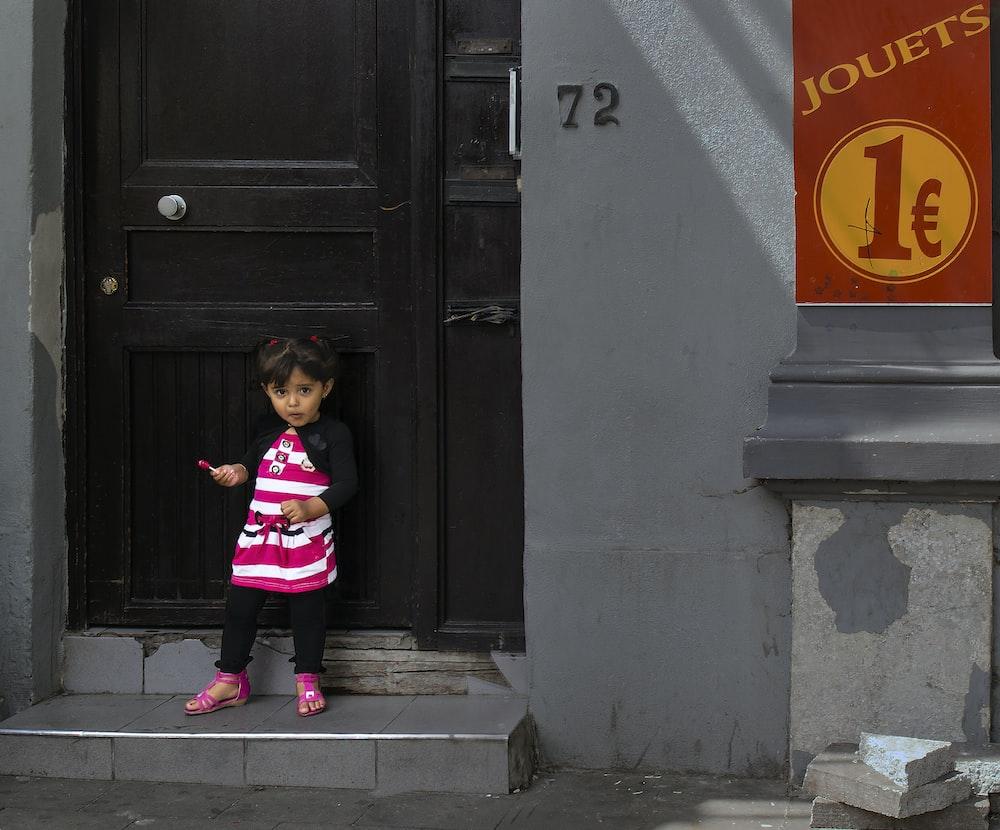 girl in pink and black jacket standing beside black wooden door