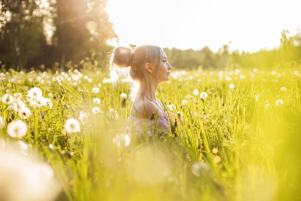 woman in black brassiere on green grass field during daytime