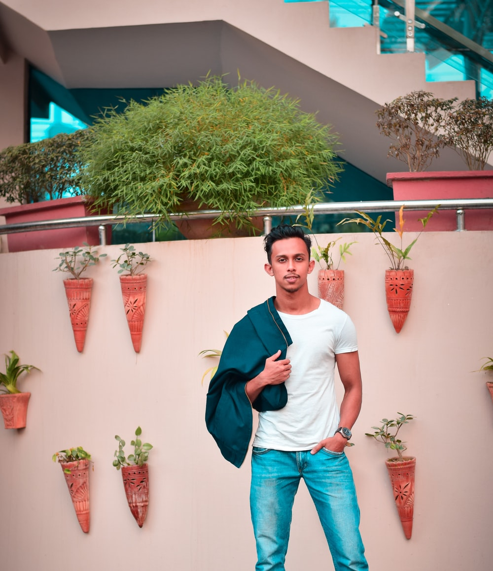 man in white crew neck t-shirt and blue denim jeans standing beside green plant