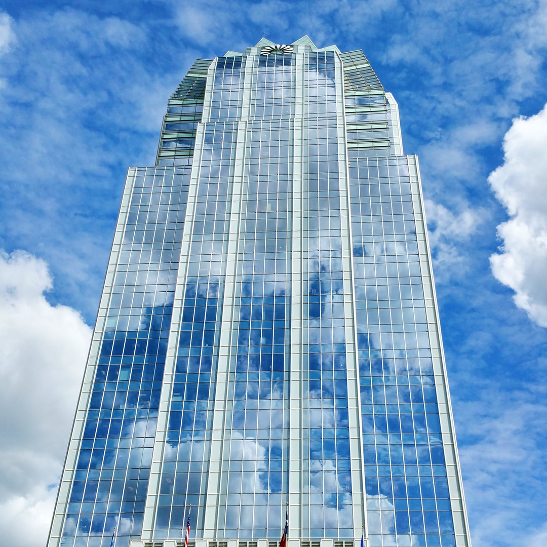 Glass facade of an office building that reflects and merges with the sky.
