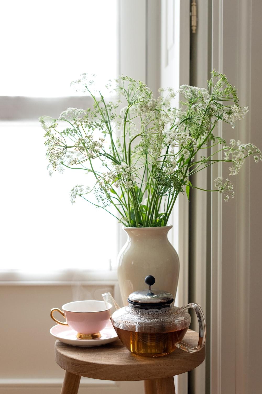 white ceramic teacup on saucer beside white flowers