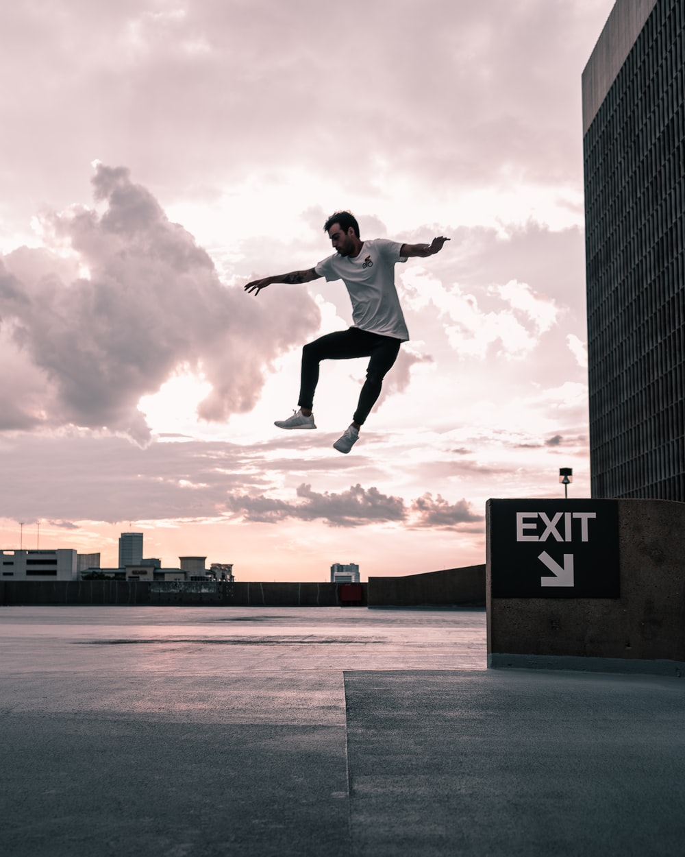 man in white shirt and black pants jumping on mid air