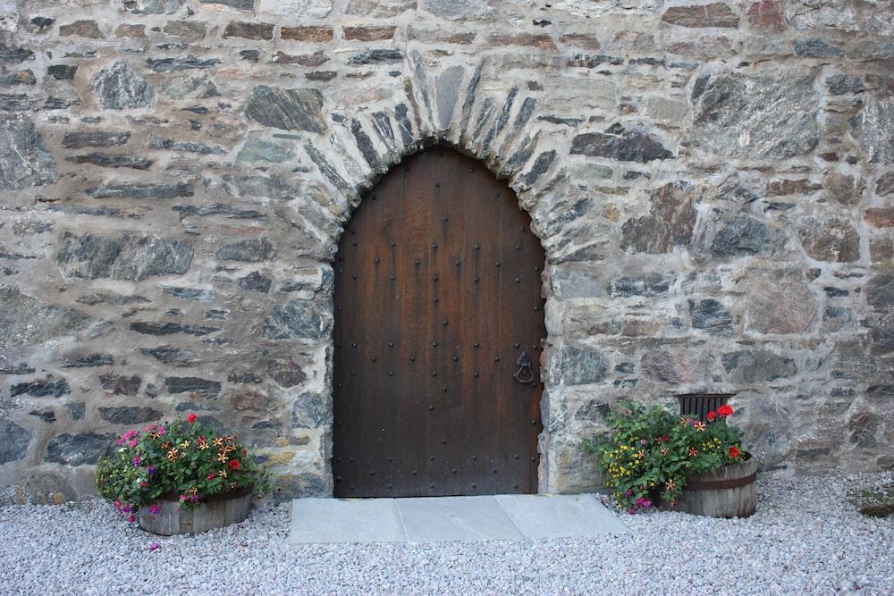 brown wooden door on gray brick wall