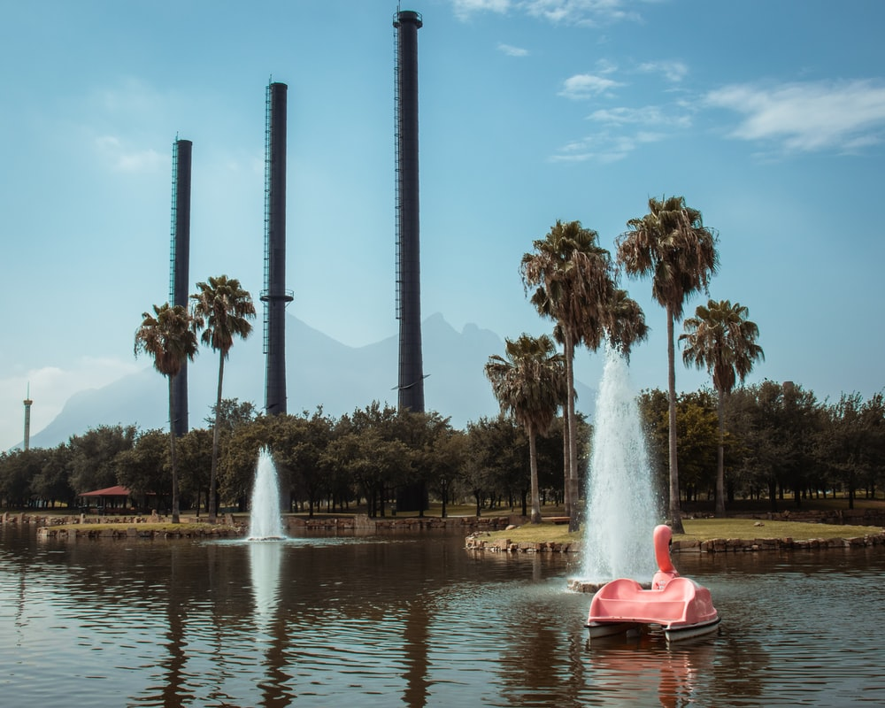 person in red kayak on water fountain during daytime