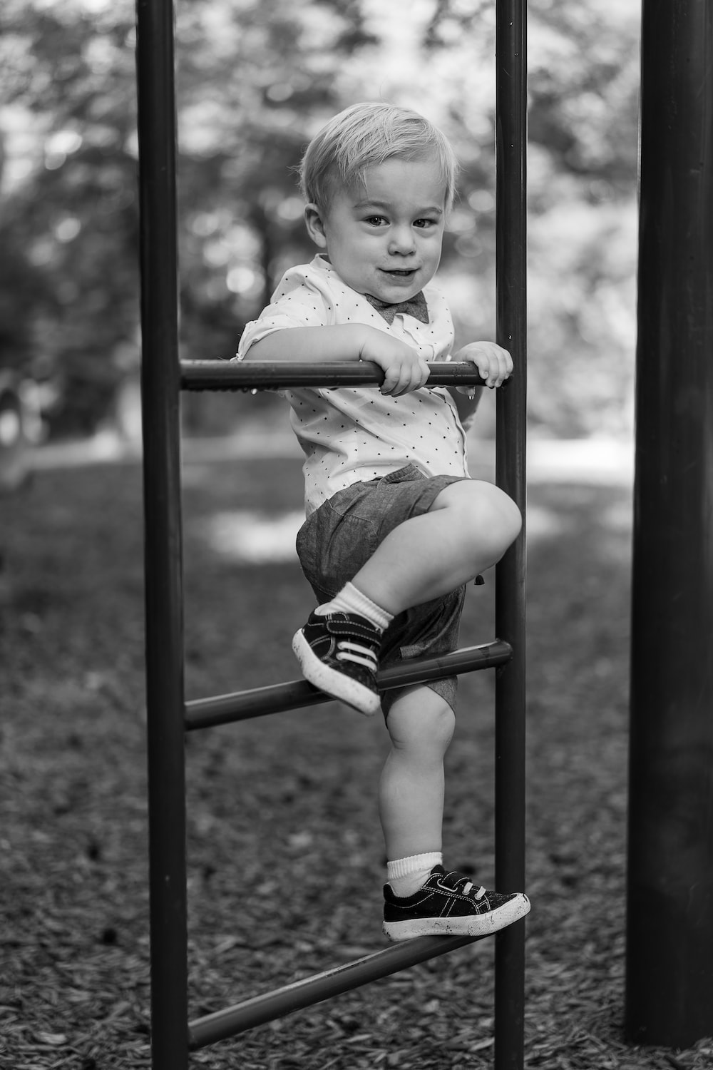 grayscale photo of baby sitting on swing