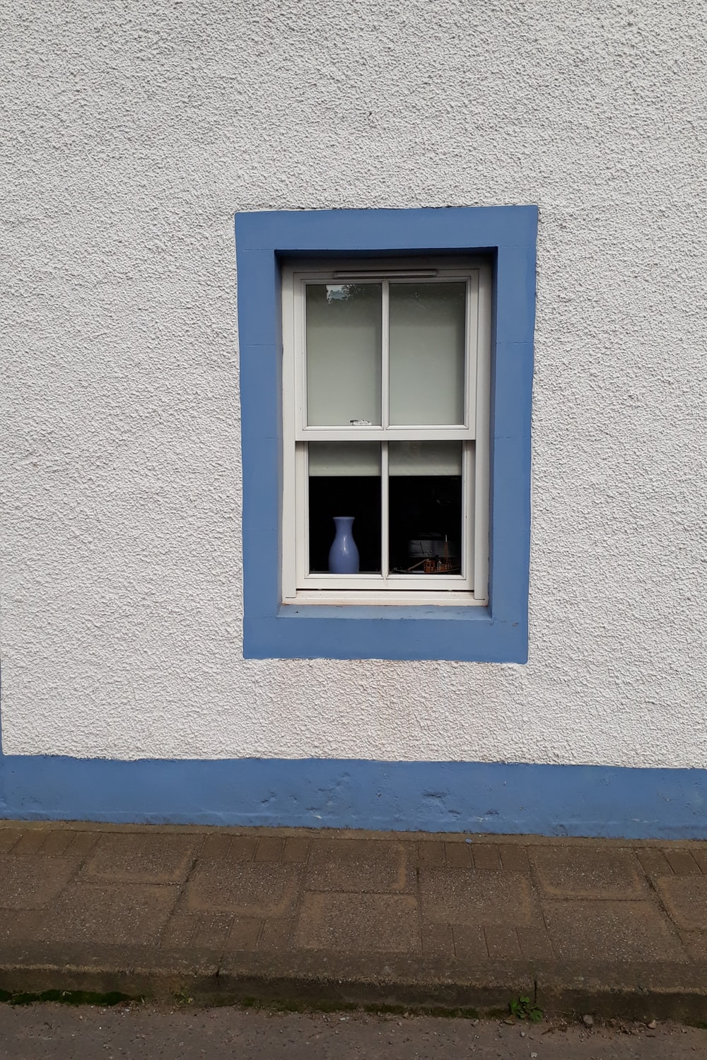 blue wooden window frame on white concrete wall
