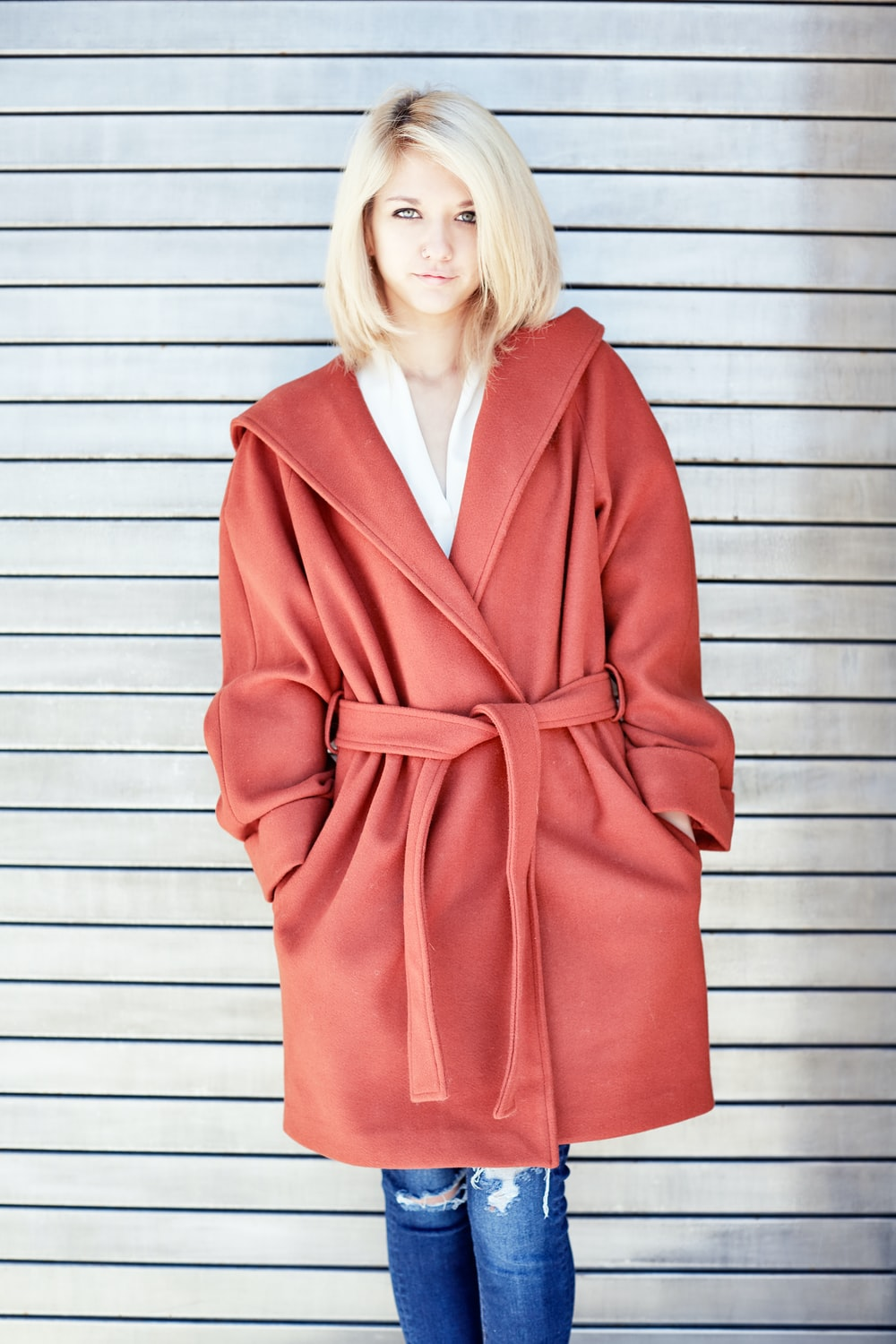 woman in red coat standing beside white wall