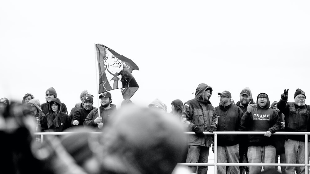 grayscale photo of man holding flag