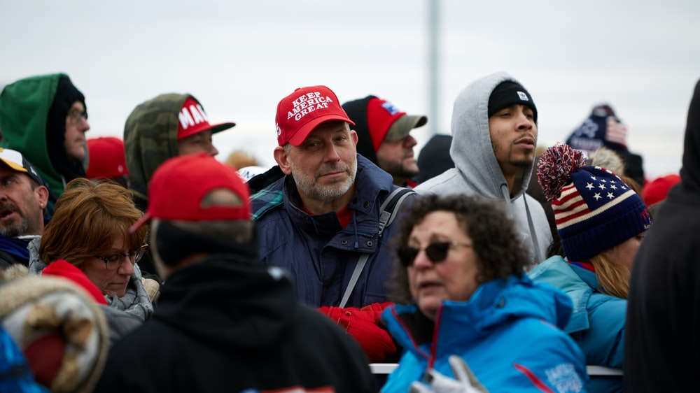 group of people in red cap and blue jacket
