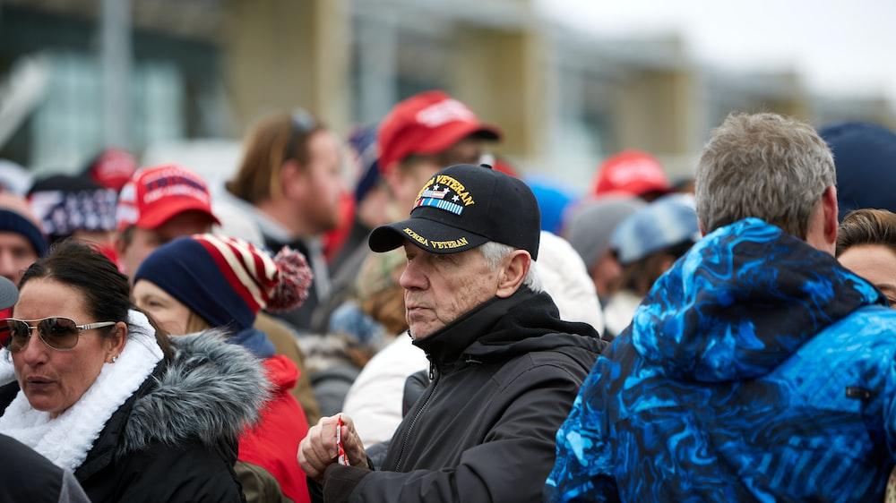 man in black jacket wearing blue cap