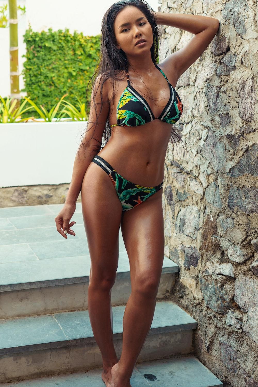 woman in black and green bikini standing on stairs