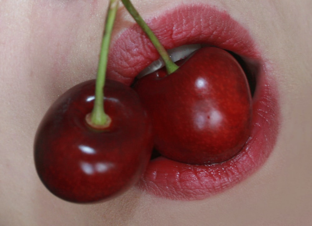 2 red cherries on white textile