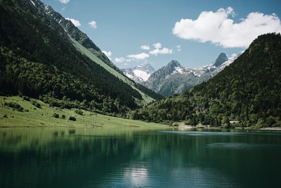 green mountains beside lake under blue sky during daytime