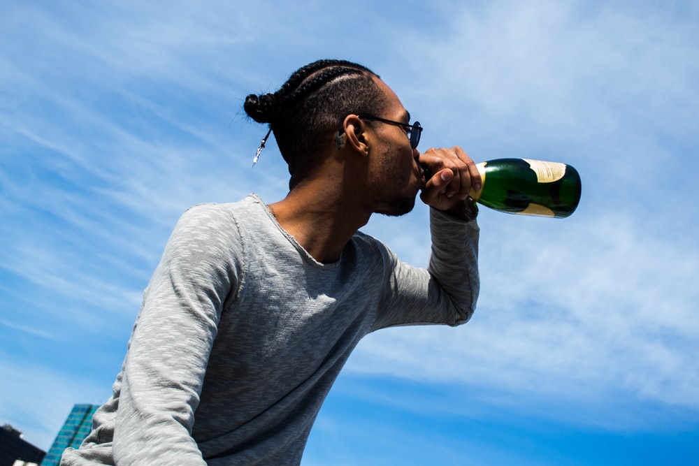 man in gray crew neck long sleeve shirt drinking green bottle under blue and white sunny
