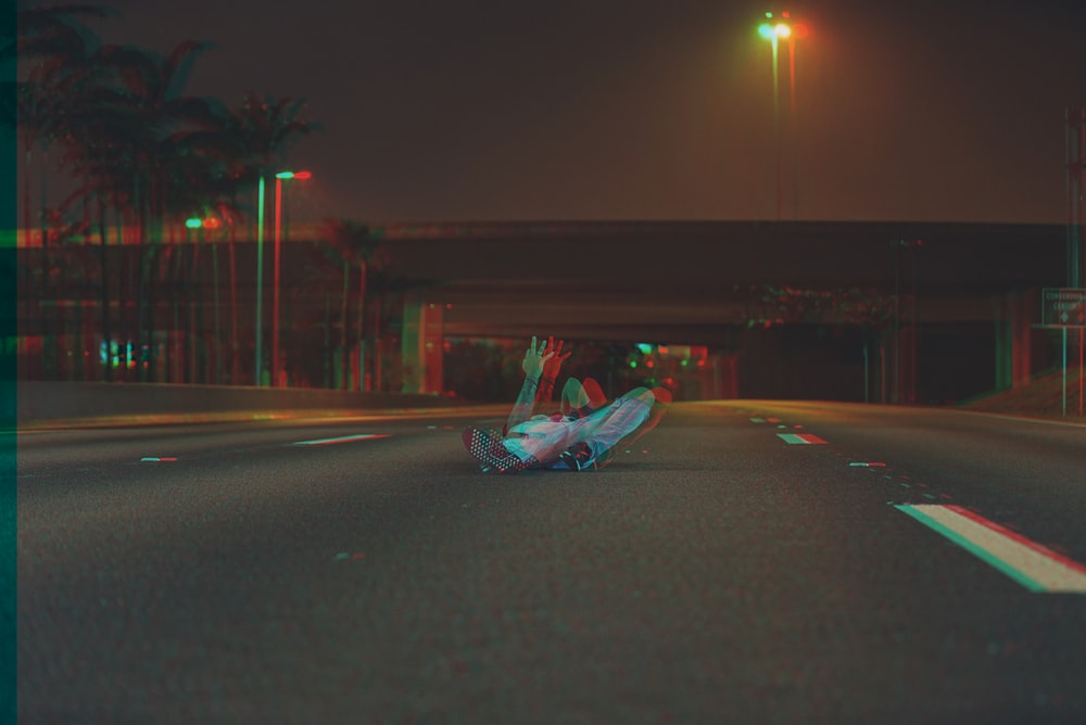 person lying on the road during night time