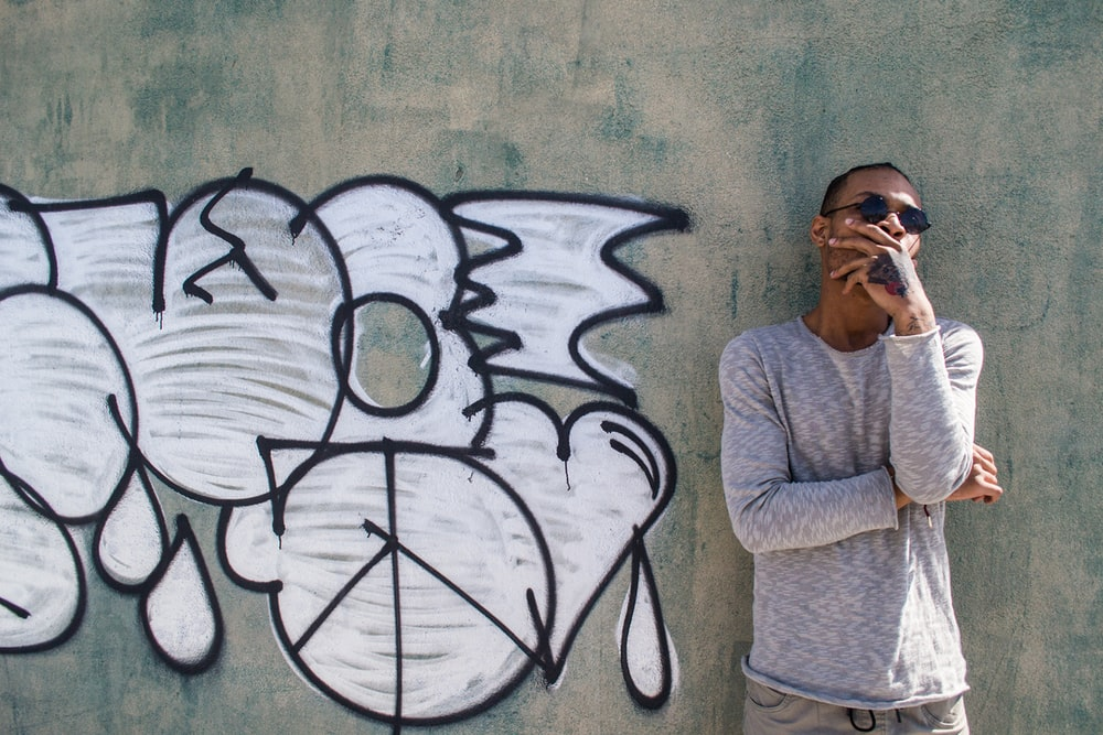 man in gray sweater standing beside wall with graffiti