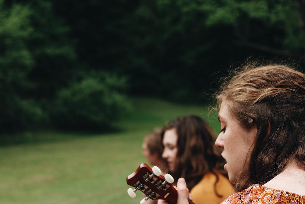 woman playing guitar during daytime