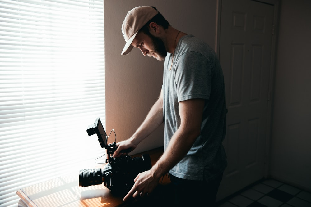 man in gray crew neck t-shirt and gray cap holding black video camera